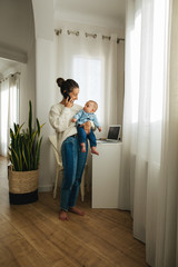 Young woman working with her baby at home.