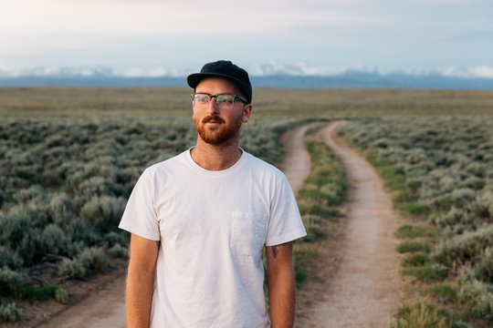 Portrait of young male in Country field prairie near mountains at sunset in western USA