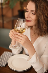 Woman with glass of wine at table in restaurant