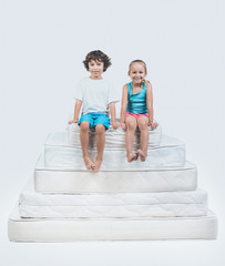 Girl and Boy Sitting on Top of Pyramid of Mattress