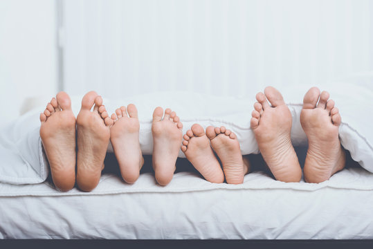 Close up Family in Bed under Cover Showing Feet