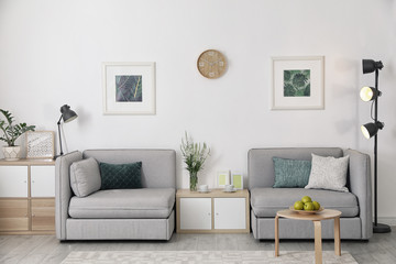 Modern interior of living room with comfortable armchairs near white wall