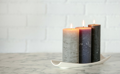 Decorative wax candles on table against brick wall