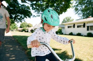 Girl on bike with training wheels