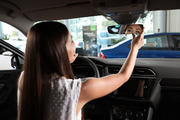 Young woman testing new car in salon