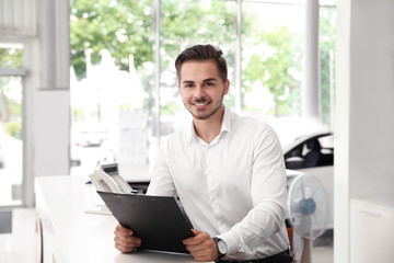 Young salesman with clipboard at desk in car salon