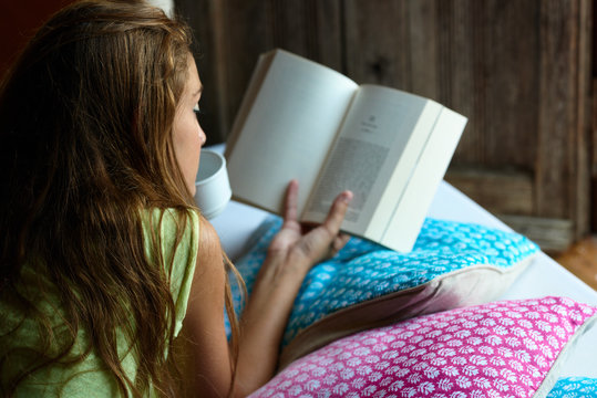 Over shoulder view of long-haired brunette girl reading a story lying on bed with colorful cushions and holding cup of coffee.