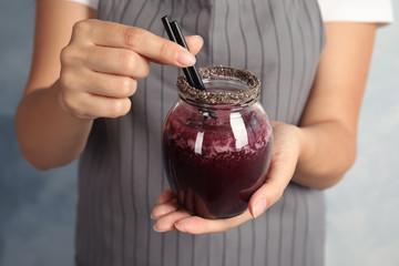 Woman holding jar of delicious acai juice, closeup