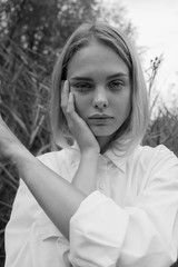 black and white portrait of beautiful blonde girl with deep eyes in a white shirt on a background of bushes