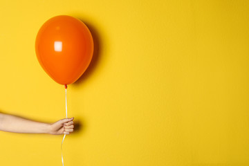 Woman holding orange balloon on color background