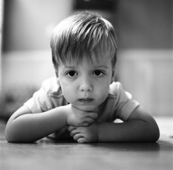 Cute young boy laying on the floor looking bored