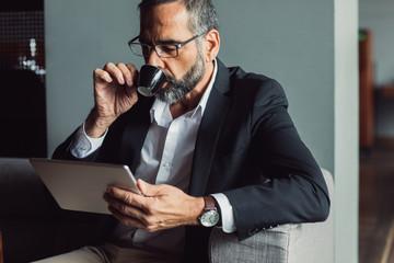 Businessman Reading on Tablet