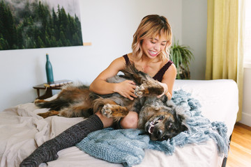 Woman on Bed Cuddling with Unique Dog