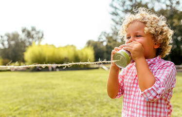 Blond curly boy playing with a toy phone made with cans and rope