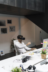 Businessman using VR viewer in office
