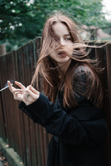 beautiful smoking young girl on a windy day
