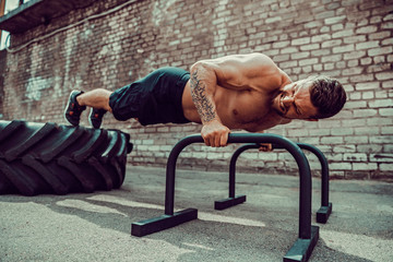 Strong sporty shirtless man doing press exercises holding plank outdoors. Push up from bar. Outdoor training, workout.