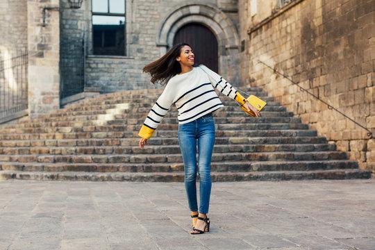 Happy stylish woman dancing on the street.