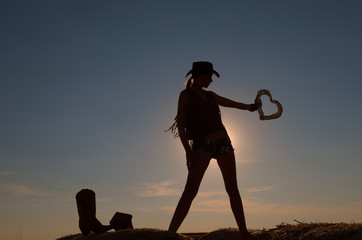 A young woman dressed as a cowgirl holds a straw heart in her hand. She takes time out and enjoys the summer sun  setting as she leisures on a hay bale.