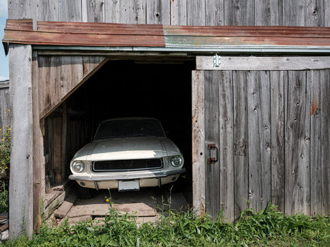 A dirt-covered classic car in a barn.