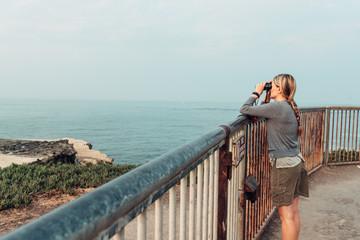Woman looking at the ocean with binoculars