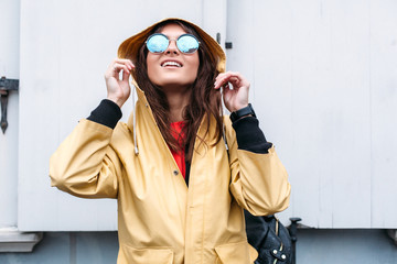 Beautiful smiling happy brunette woman posing on the street in rainy day, dressed in yellow raincoat and mirror style sunglasses