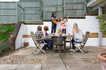 Father and daughter playing their guitars to family members on the patio area of their garden.