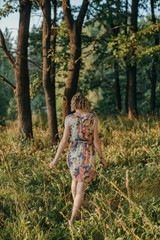 Back view portrait of young blond unrecognizable woman walking by the summer forest