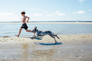 Boy runs on the beach with his dog