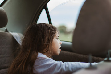 Girl curiously look out the window of car