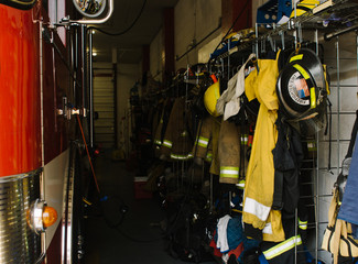 Fire fighters' gear hanging on wall in firehouse