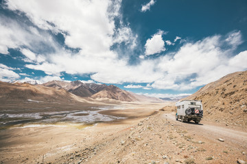 camping truck in rugged mountain landscape on the pamir highway - tajikistan