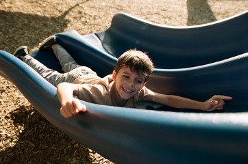 boy sliding down slide backwards