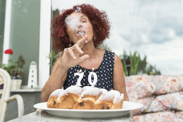 Badass senior woman smoking on a birthday cake