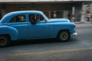 Habana, Cuba - 10 January, 2017:old blue car driving on a cuba street on a beautiful day with some people on the sidewalk