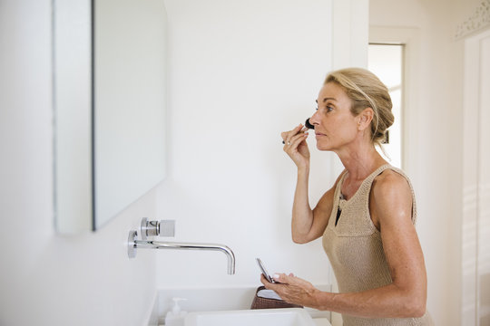 Woman putting face powder to her face