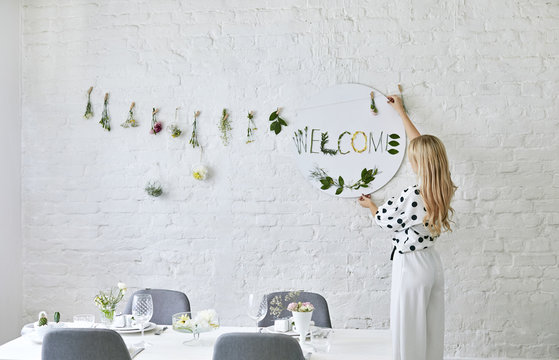 Woman Putting Decoration on the Wall