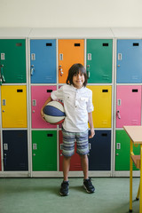 Elementary School Pupil with Ball In Front Of Colorful Lockers