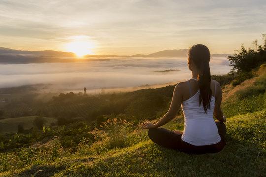 Peaceful woman meditating on a mountain at sunrise