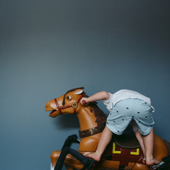 Little boy riding toy horse in bedroom