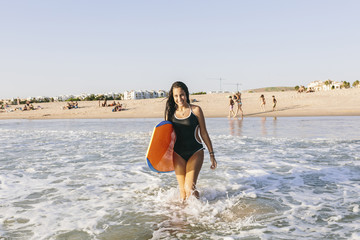Cute teen girl with a bodyboard at the beach
