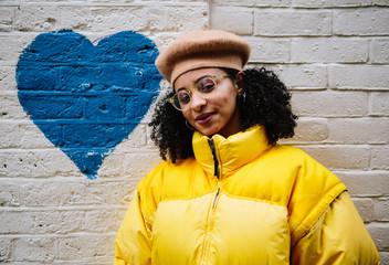 Beautiful mixed ethnicity woman wearing thick yellow puffer jacket