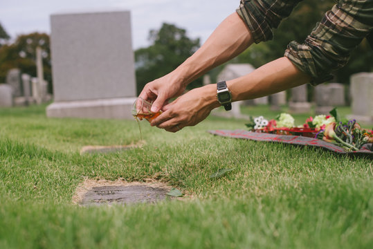 Pouring whiskey over grave in cemetery