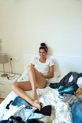 Laughing pretty girl sitting on messy bed.