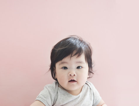 Cute little baby girl with pink background