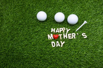 Happy mother's day with three golf balls are on green grass background