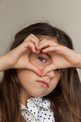 Pretty young girl making a heart shape around her blue eye