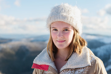 pretty teen girl in beanie and jacket, with mountain landscape i
