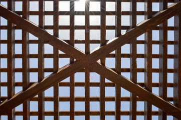 Texture of a brown wooden abstract lattice with square cells with holes from boards of log beams arranged vertically horizontally diagonally against the background of the sun and sky. The background
