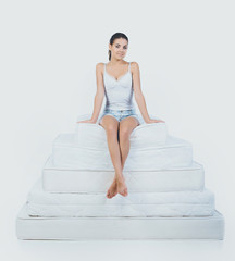 Young Smiling Woman Sitting on Pyramid of Mattress
